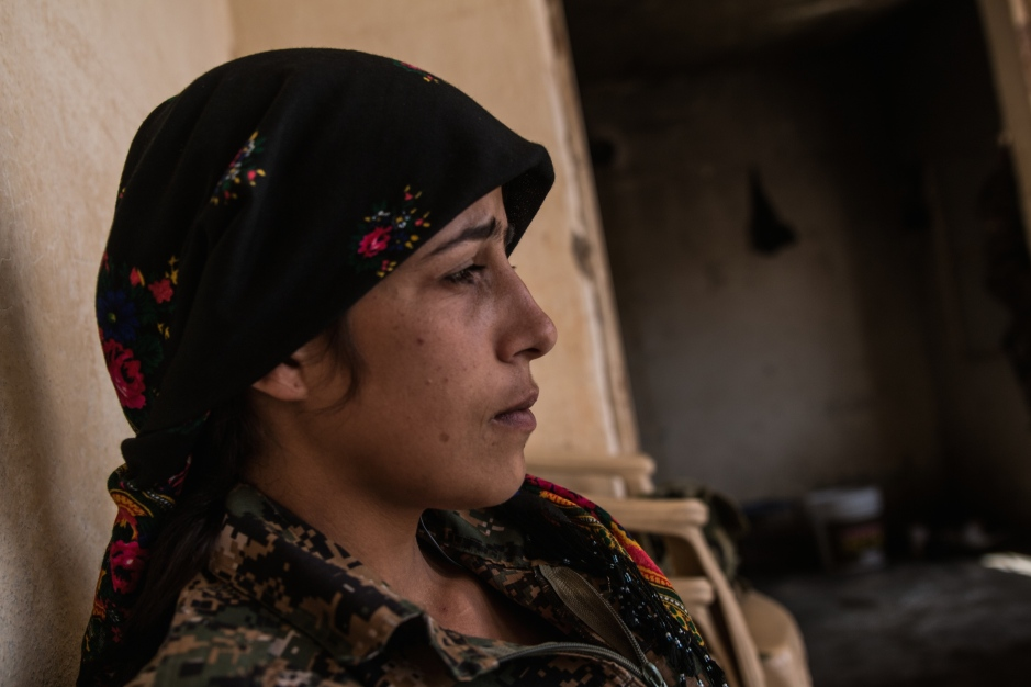 A YPJ fighter reflects whilst waiting for the upcoming assault on ISIS territory
