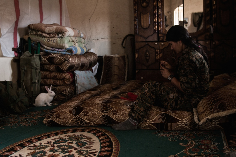 Hundreds of miles away from her family, a young female fighter finds comfort in the company of a pet rabbit as she cleans her weapon