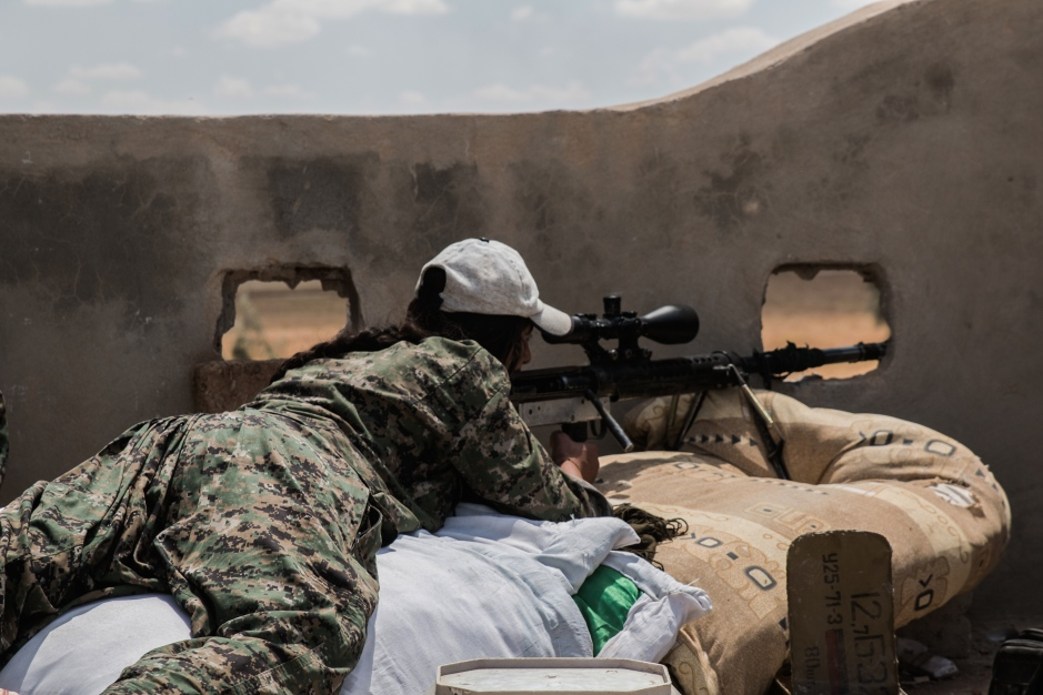 A female sniper and veteran of the PKK takes aim at ISIS fighters in a nearby village with a homemade 'shiyar' rifle