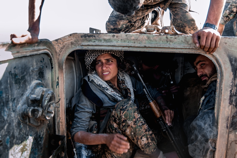 In the final push to try and break into the ISIS-held village, a female fighter mounts up with her male comrades into a Russian-made BMP armoured personnel carrier. Much of the armour used by the YPG and YPJ has been taken from ISIS and subsequently repaired in Qamishli town