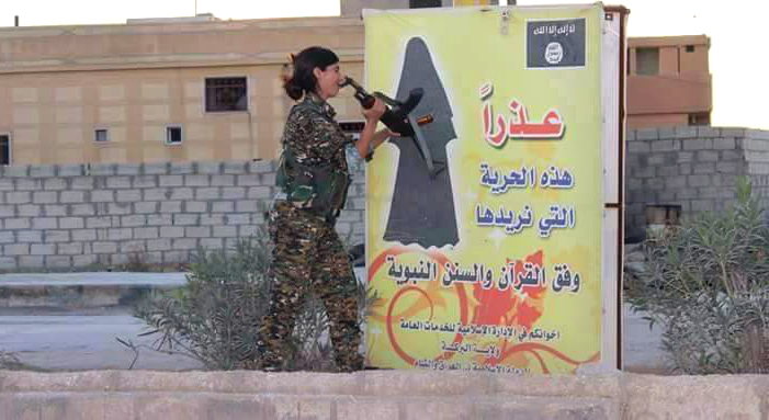 A Kurdish female fighter breaks a banner calling for freedom of women by wearing Niqab