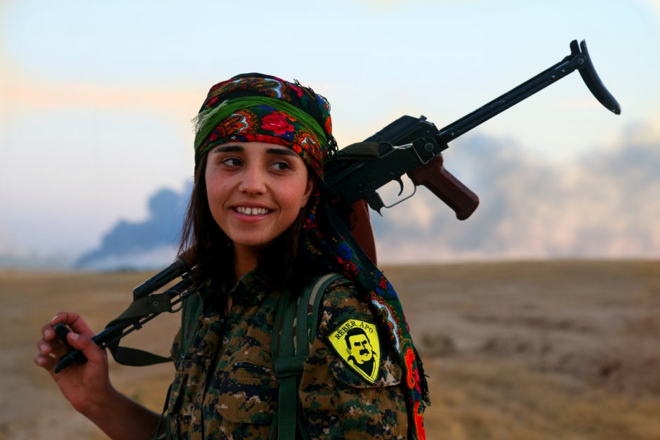 A Kurdish YPJ fighter with smoke behind her from one of the areas where under ISIS control in the town of Al Hol, Hasakah. Photo credit: Delil Souleiman
